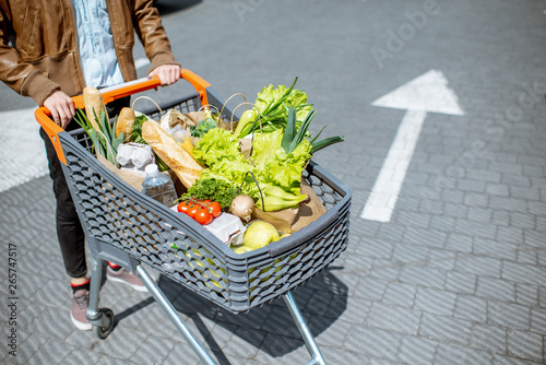 Fototapety, obrazy: Man riding shopping cart full of fresh and healthy products outdoors, close-up view