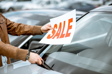 Salesperson putting sale plate on the car windshield on the open ground of a dealership, close-up view