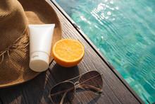 Orange Juice, Straw Hat, Sunblock And Sunglasses By Poolside