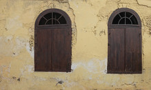 Old Wooden Half Circle Arched Windows. Dark Wood Half Moon Windows With Cream Pastel Yellow Color Damage Aged Brick Wall
