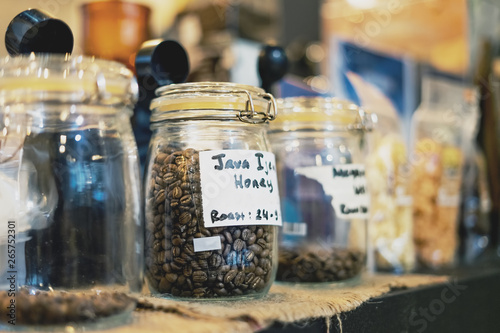 In de dag Apotheek Coffee Bean in Glass Jar. Arabica Coffee Variant Java Ijen Raung with Honey Process and Roast in Glass Container at Store Front or Cafe. Selective Focus.