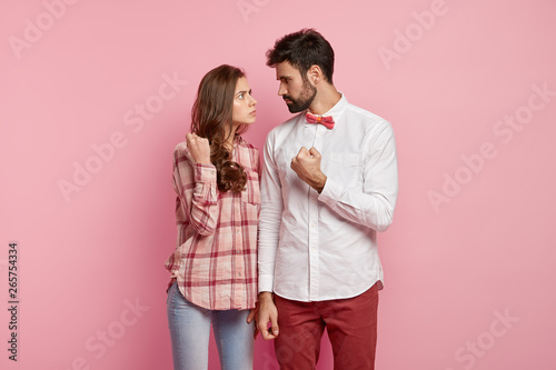 Poster de jardin Kiev Angry husband and wife look strict at each other, show fists, have quarrel, dressed in stylish outfit, sort out relationships, decide about house duties, gesture angrily, stand against pink background