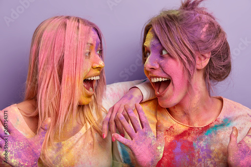 Photo Horizontal shot of two happy women with colored hair, body and clothes, celebrate Holi Color festival, look happily at each other, pose over purple background
