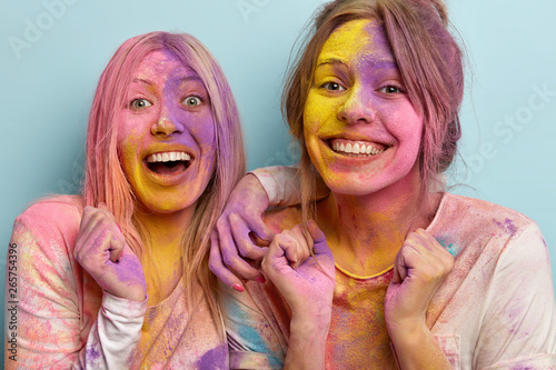 Photo  Headshot of positive cheerful two women with toothy smile on faces, have dirty colored skin, raise hands clenched in fists, celebrate annual spring Holi festival, express good emotions