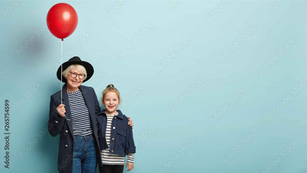 Fototapety, obrazy: Senior grey haired woman in hat and stylish outfit embraces small kid, holds red helium balloon, feel happy, celebrate Children Day together, embrace and smile, isolated over blue studio wall