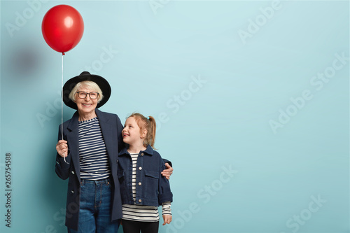 Obraz Indoor shot of fashionable senior woman embraces little child, enjoy spending time together, celebrate first day at school, hold air balloon, pose over blue background with blank space on right - fototapety do salonu