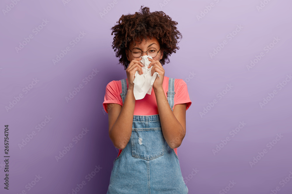 Fototapety, obrazy: Portrait of sick African American woman sneezes in white tissue, suffers from rhinitis and running nose, has allergy on something, looks unhealthy, feels unwell. Symptoms of cold or allergy.