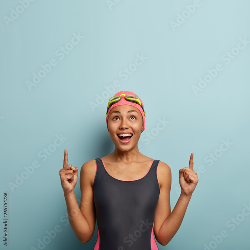 Vertical photo of joyous dark skinned female enjoys favourite hobby and summer active rest, dressed in swimsuit, goggles on forehead, points above on free space, advertises something happily Wall mural