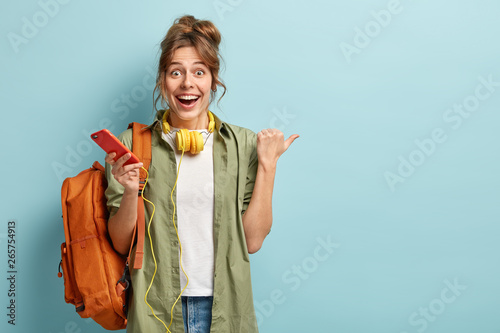 Joyful European girl checks nootification or email box on cellular, enjoys listening favourite music in headphones, has surprised happy reaction on something aside, points thumb at free space - 265754913