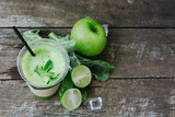 Green apple smoothie in glass and kale leaves on wooden table - 265755116
