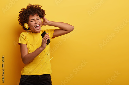 Pleased stylish dark skinned girl enjoys music from motivation playlist, enjoys free time for listening popular tracks, sings loudly words of song, closes eyes from satisfaction, wears yellow t shirt - 265755348
