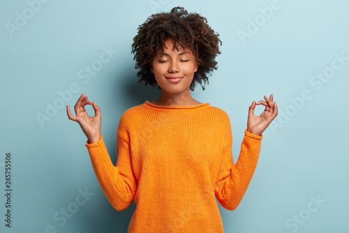 Cuadros en Lienzo Mindful peaceful Afro American woman meditates indoor, keeps hands in mudra gest