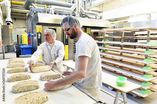 Foto Arbeiter am fliessband in einer Großbäckerei - Herstellung von Brot in einem Wer