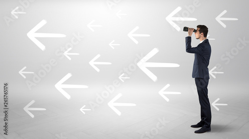 Valokuva  Young businessman standing and looking through binoculars with drawn arrows arou