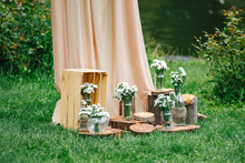 Wedding Decorations And Arch. Jars With Flowers. Rustic Wedding Decoration With Flowers. Old Wooden Style. Romantic Picnic In Nature