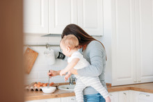 Young Mother Brunette Woman With Baby Boy In Arms Cooking Food In White Modern Kitchen At Home