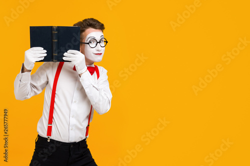 Fotografie, Tablou  portrait of mime man artist reading book isolated on yellow background