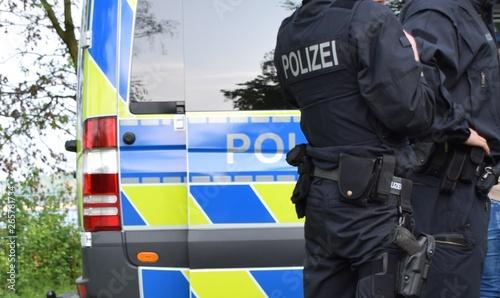 Fototapeta Bewaffnete Polizisten in schwarzer Uniform vor einem Polizeiauto