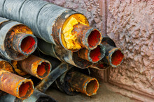 Water Pipeline Repair. Rusty Steel Pipe With Insulation On The Construction Site In A Plastic Tube Wrapper Lying On The Yard In A Bunch Horizontally. Rusty Old Pipeline Stacked Up