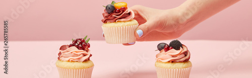 Photo panoramic shot of woman with sweet cupcakes on pink