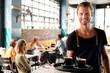 Leinwandbild Motiv Portrait Of Waiter Serving Customers In Busy Coffee Shop