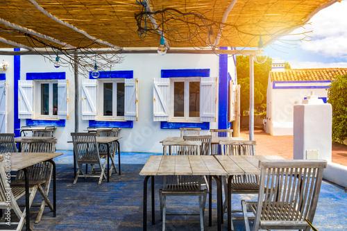 Foto auf AluDibond Gezeichnet Straßenkaffee Restaurant tables with chairs on terrace near Praia da Rocha beach on coast of Portimao, Algarve, Portugal. Tables on terrace in small coastal restaurant with sea view near Portimao town, Portugal.