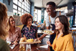 canvas print picture Waiter Serving Group Of Female Friends Meeting For Drinks And Food In Restaurant