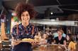 Leinwandbild Motiv Portrait Of Waitress Serving Food To Customers In Busy Bar Restaurant