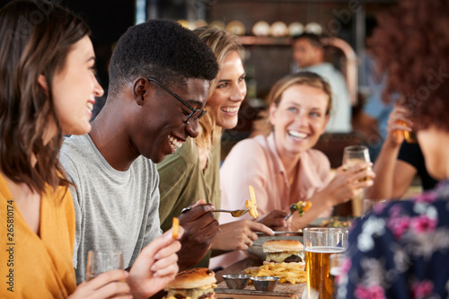 Group Of Young Friends Meeting For Drinks And Food In Restaurant - 265810174