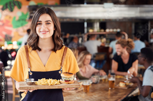 In de dag Restaurant Portrait Of Waitress Serving Food To Customers In Busy Bar Restaurant