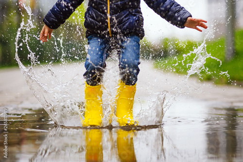 Fototapeta legs of child with yellow rubber boots jump in puddle on an autumn walk