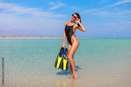 Fotoposter Ontspanning Travel portrait of enjoying female outdoors on the coast on Red Sea, Egypt. Happy woman in exotic bikini with snorkeling equipment mask and flippers. Luxury sport tourism concept in tropical country.