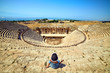 Leinwanddruck Bild - Back view of woman traveler in hat looking at amazing Amphitheater ruins in ancient Hierapolis, Pamukkale, Turkey. Grand panorama
