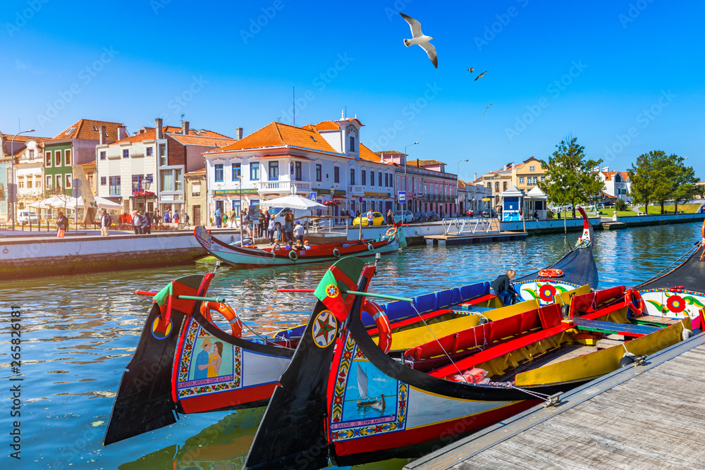 Fototapeta Traditional boats on the canal in Aveiro, Portugal. Colorful Moliceiro boat rides in Aveiro are popular with tourists to enjoy views of the charming canals. Aveiro, Portugal.