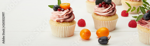 panoramic shot of cupcakes with fruits and berries on white surface Wallpaper Mural