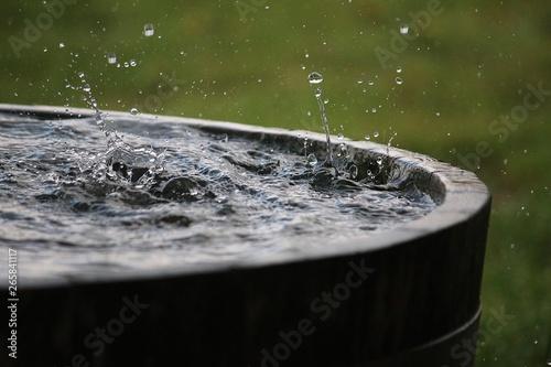 Fototapeta rain is falling in a wooden barrel full of water in the garden