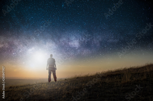 Photo Stands Black A science fiction concept. A man standing on a hill lookin gout across space with a bright light in the sky.