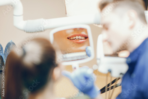 A young and beautiful girl treats her teeth with a dentist
