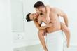 canvas print picture - happy shirtless man piggybacking cheerful brunette girlfriend in black underwear