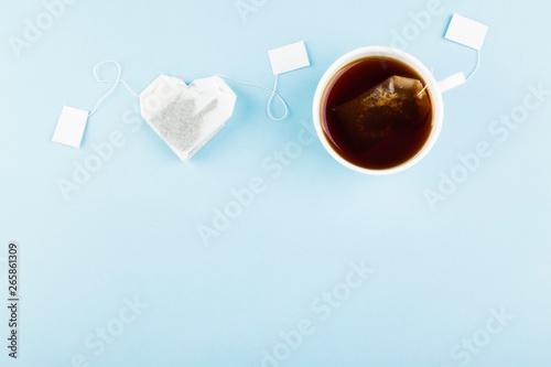 Fototapeta Cup of tea and tea bags in form of heart on blue background. Top view, copy space. Food background obraz na płótnie