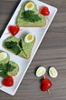 Sandwiches for breakfast. Heart-shaped bread slices smeared with ground avocado. Decorated with boiled quail eggs, parsley and tomatoes. Unfolded on a white rectangular plate.