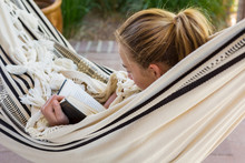 13 Year Old Girl Reading In A Hammock
