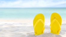 Yellow Flip Flops On Beach Sand Texture And Tropical Sea Background. Summer Holidays And Hot Season. Fun Ocean Weekend. Summertime. Selective Focus. Banner
