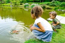 A Young Girl And Boy Sit By A Pond At A Public Park