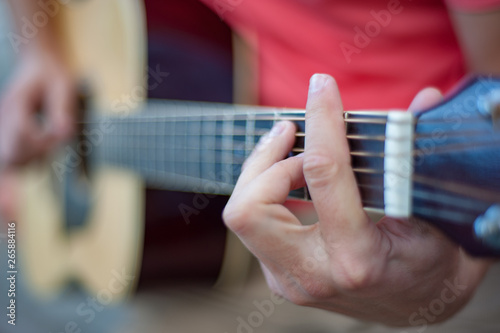 Stampa su Tela  Man playing guitar , close up