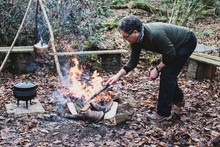 Man Standing In A Forest, Stoking Campfire, Wooden Tripod And Cast Iron Metal Pot.