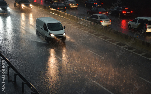 Fototapeta  delivery van speeding by highway in rainy night