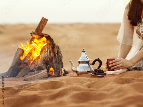 Dates, teapot, cup with tea near the fire in the desert with a beautiful backgro Canvas Print