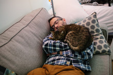 Man Sleeps On Couch With Tabby...