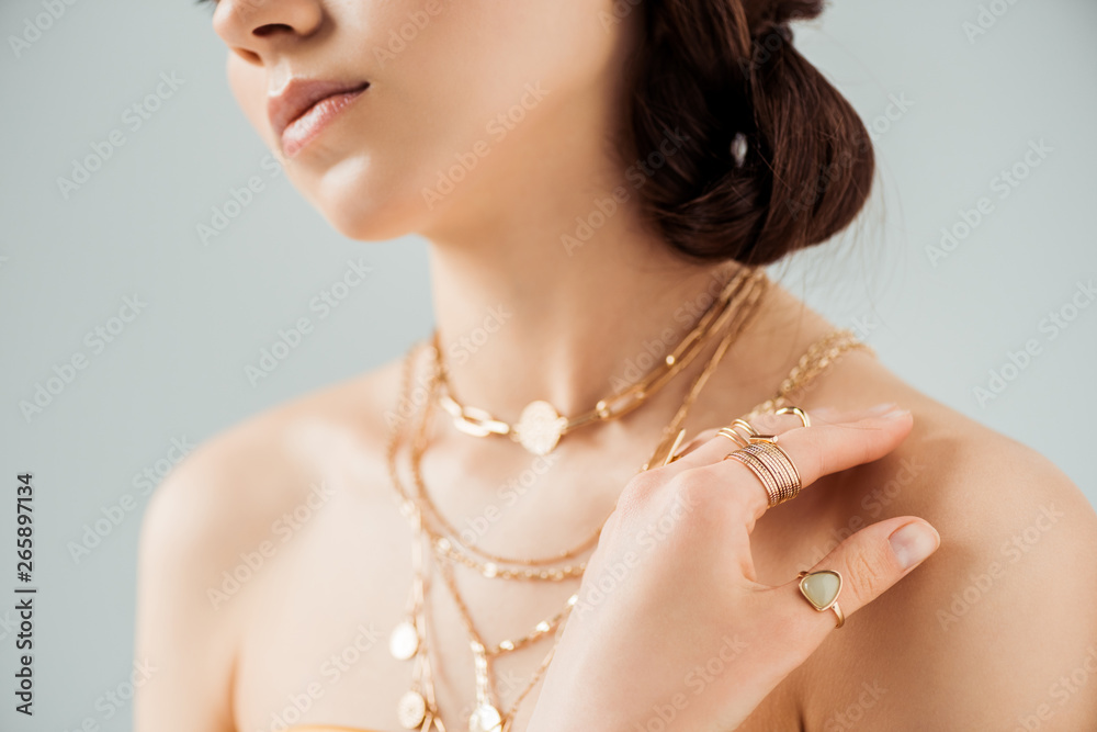 Fototapeta cropped view of young woman with shiny lips in golden necklaces and rings isolated on grey